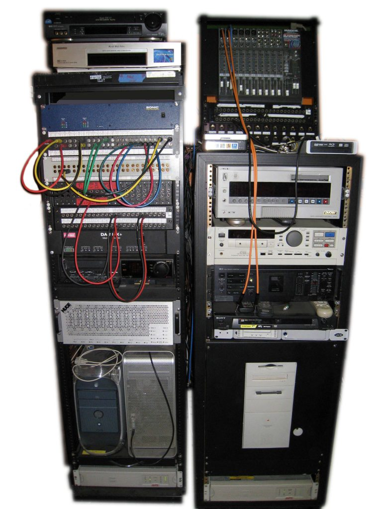 Two equipment racks with various vintages of computers and storage plus analog and digital audio and video gear with patching